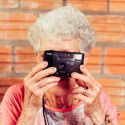 Stichting De Tijdmachine: Onze filosofie en aanpak - Oudere dame maakt foto